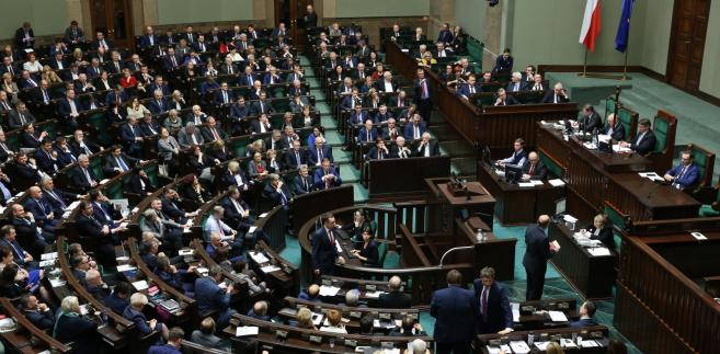 Poslowie głosują podczas posiedzenia Sejmu