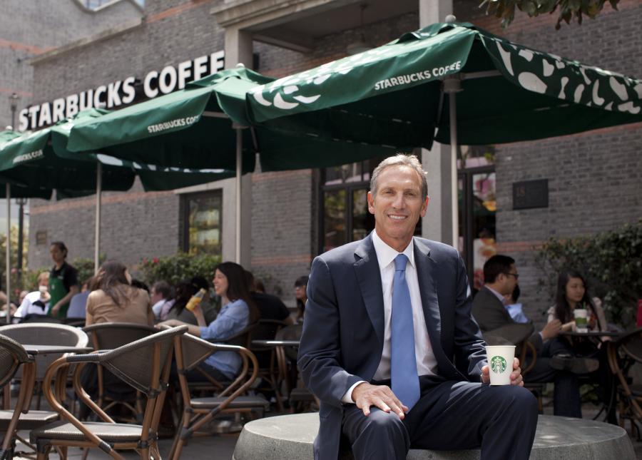 Howard Schultz, dyrektor Starbucks Crp., pozuje do zdjęcia na zewnątrz jednej z firmowych kawiarni w Szanghaju, Chiny.  Starbucks wprowadza coraz szerszą ofertę po tym, jak zanotował większy niż przewidywany wzrost sprzedaży kawy Via.